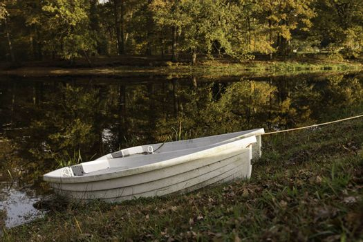 two boats in a pond in the autum forest with red brown and golden colors in national park de veluwe in holland