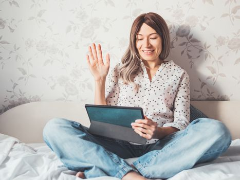 Woman sits on bed with tablet PC. She greets somebody via online video call or conference. Distant learning, remote education. Self isolation during quarantine.