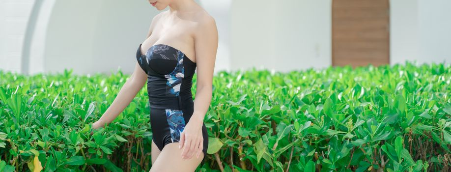 Body part of woman in one piece swimsuit with view on garden and