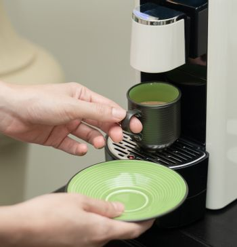 Machine serving coffee in a cup. Coffee capsule machine maker.