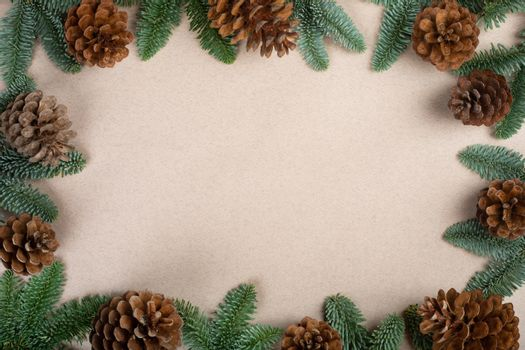 Traditional green christmas tree noble fir and cones border frame on craft paper background copy space for text