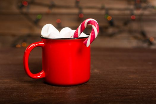 Cocoa in red mug with marshmallows and candy cane on dark wooden background with bokeh lights
