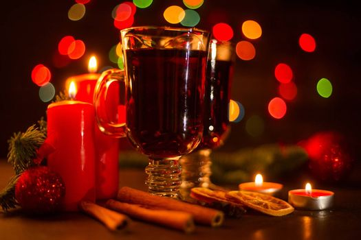 Mulled wine with cinnamon sticks orange candles fir tree branch and baubles over holiday christmas lights background