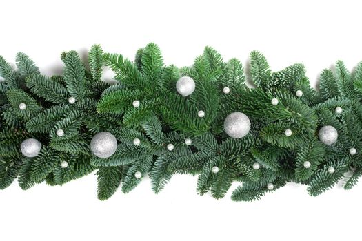 Christmas Border frame of natural noble fir tree branches and silver baubles isolated on white background