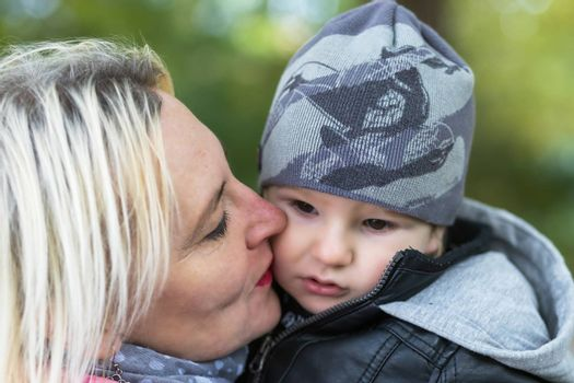 Closeup view of young grandmother kissing on the cheek her little grandson outdoors.