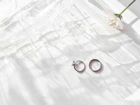 Top view on wedding and engagement rings with diamond. Symbol of love and marriage on white background with laced shadow. Sunlight on white background.