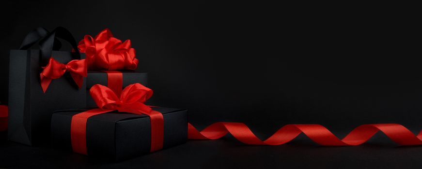 Gift box wrapped in black paper with red ribbon on black background, design banner black friday sale concept copy space for text