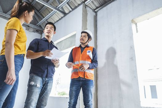 Young asian couple checking house with foreman engineering home inspection building house Walk home inspection with looking and pointing construction for check building home on job site to customers