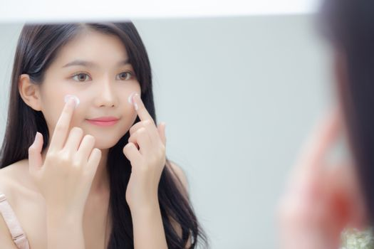 Beautiful young asian woman smiling look at mirror of checking f