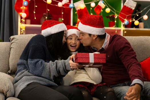 Happy family smile together with a gift box in their home with decorated interior during Christmas