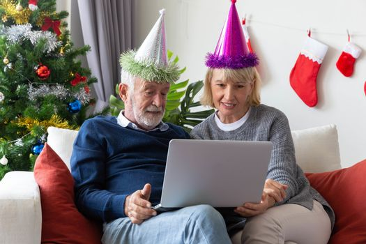 Senior retirement couple connect computer laptop  during Christmas celebration in their living room