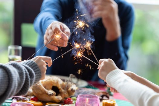 A family celebrate Christmas time together with dinner and sparkling during dinner - focus at sparkler