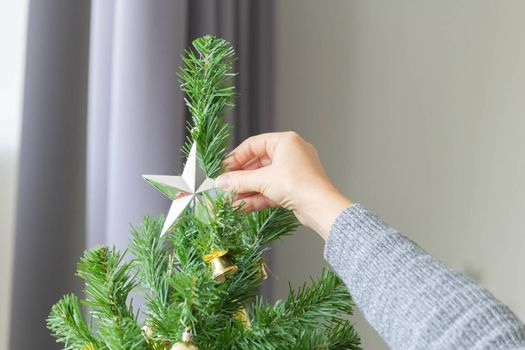Closeup of woman hand decorate the Christmas tree for Christmas pary