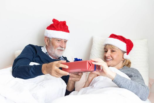Senior couple exchange gift in their bed during the christmas