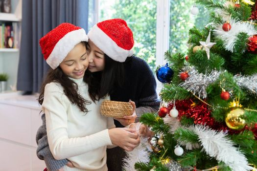 Mom kiss her daugher while decorate the christmas tree during the christmas holiday