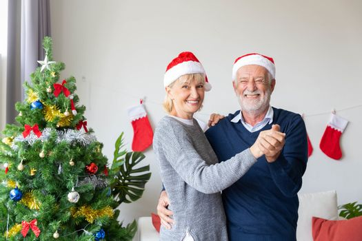 Senior retirement couple happy dancing in living which decorated by Christmas tree during the Christmas time