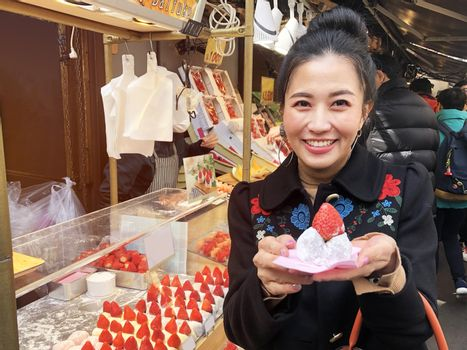 Tourist woman showing street food strawberry Daifuku, Strawberry Mochi at Tsukiji Fish Market in Tokyo.