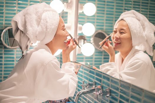 Young woman putting on makeup after shower