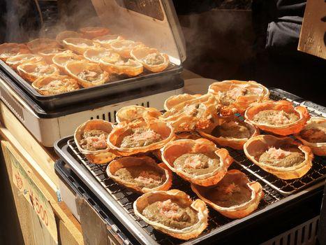 Gril crab brain street food in morning  at tsukiji fish market in tokyo, japan