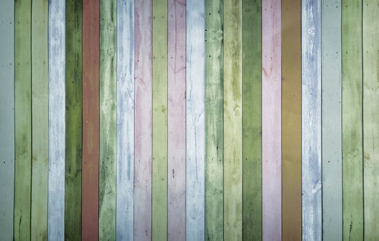 Colorful background image with a pattern of multi-colored vertical stripes with an imitation of a painted wooden surface