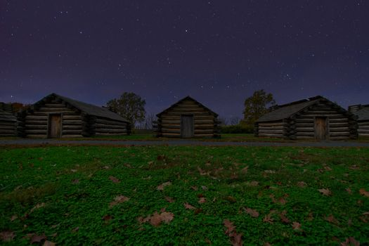 Reproduction Log Cabins at Valley Forge National Historical Park With a Night Sky Full of Stars Behind