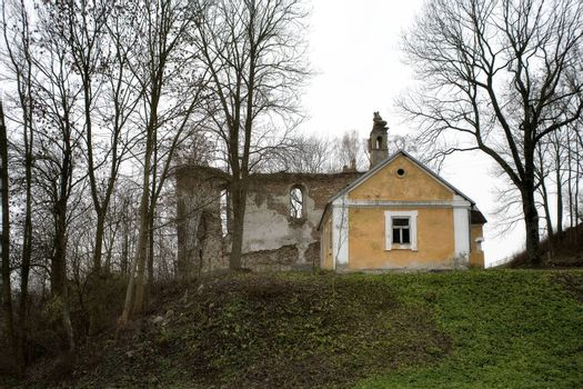 old historic house with wall ruins on gray november day in Podla