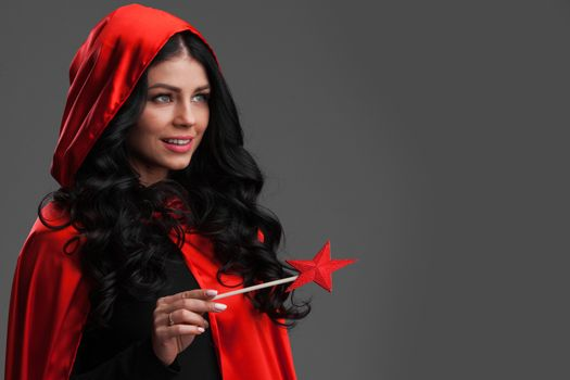 Woman in red cape with magic wand
