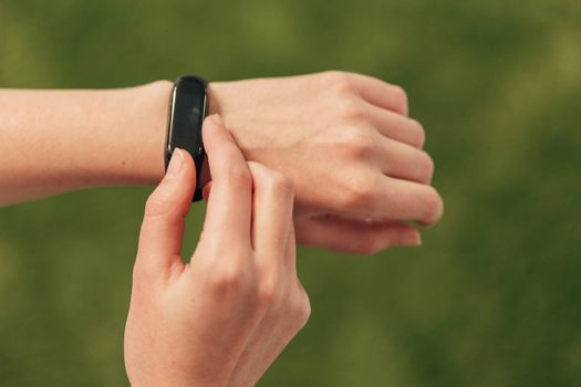 A smartwatch on a woman's hand measures the heartbeat. Checking the pulse after fitness.