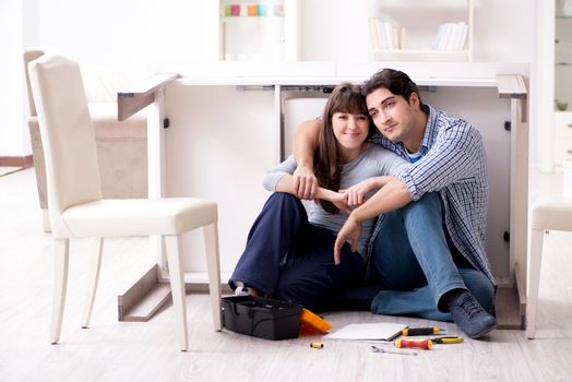 Man and woman assembling furniture at home
