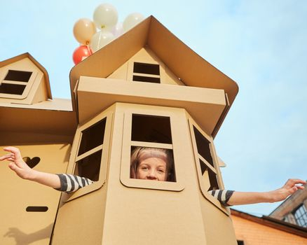 Child playing in a cardboard playhouse. Eco concept