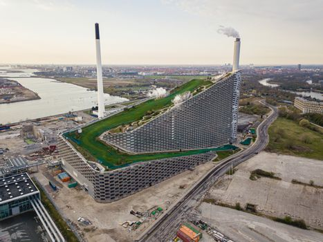 Copenhagen, Denmark - April 12, 2020: Aerial drone view of Amager Bakke, a waste to power plant with a ski slope on top.