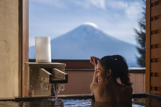 Beautiful woman enjoy onsen (mineral hot bath) in morning and seeing view of Fuji mountain in japan