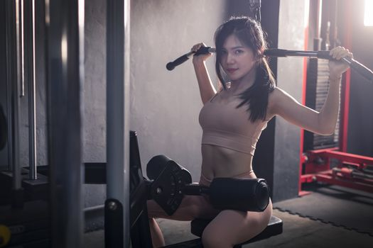 young fitness woman workout with exercise-machine in gym