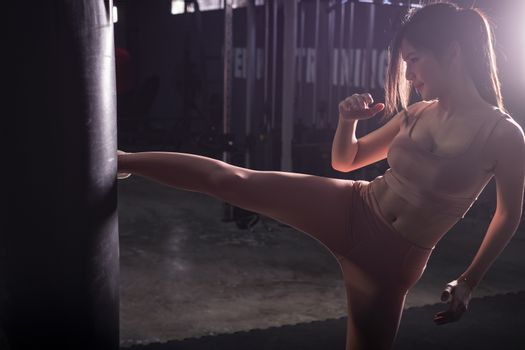 Fitness girl doing kick boxing training in sport gym