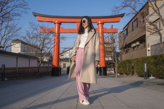 Young woman tourist travel Kyoto, Japan at Fushimi Inari Shrine main gate at sunrise