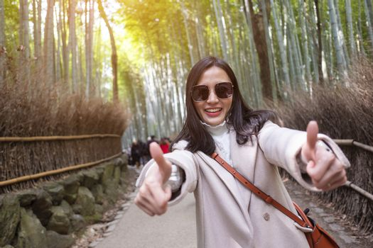 Asian woman traveling at Bamboo Forest in Kyoto, Japan.