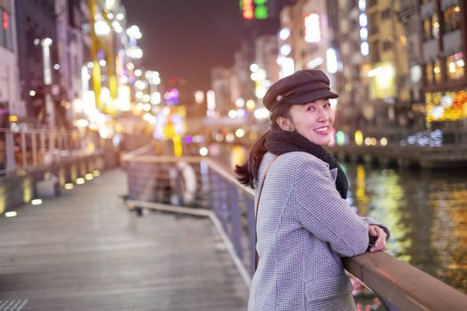 Beautiful smiling woman tourists traveling in walking at street shopping center Dotonbori in Osaka, Japan.