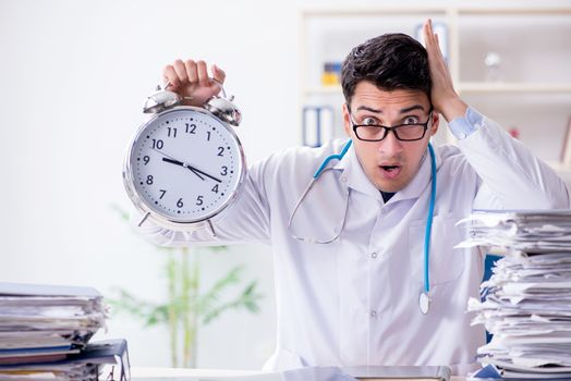 Doctor with alarm clock in urgent check-up concept
