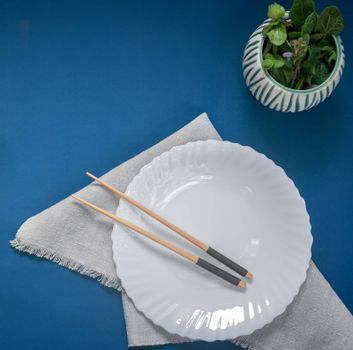 On the table on a napkin is an empty white plate with wooden chopsticks on it. Sample of Japanese cuisine. The view from the top, flat lay