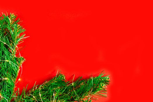 green pine branches with light bulbs on a red background frame the corner of the Christmas background, holiday lights