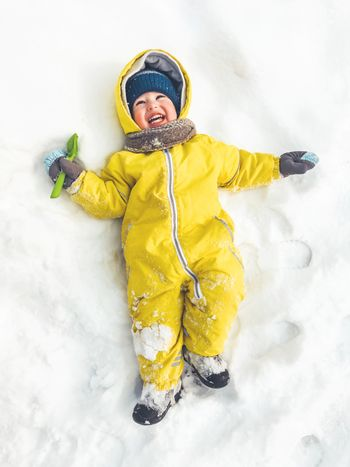 Smiling toddler in bright yellow jumpsuit is lying on snow. Laughing child walking outdoors in snowy weather. Top view on happy kid in colorful overall suit. Winter season.