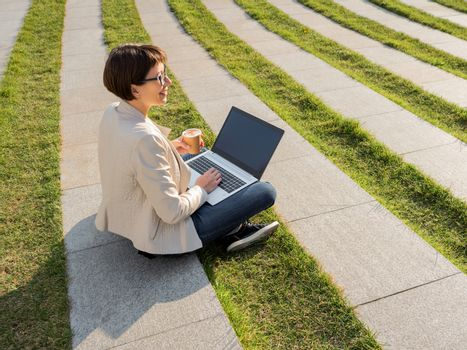 Freelance business woman sits in park with laptop and take away cardboard cup of coffee. Casual clothes, urban lifestyle of millennials. Working remotely.