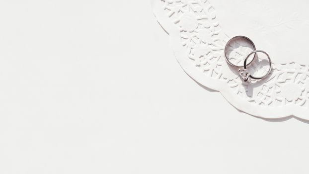 Top view on wedding and engagement rings with diamond on laced napkin. Symbol of love and marriage on white background. Sunlight on white background.