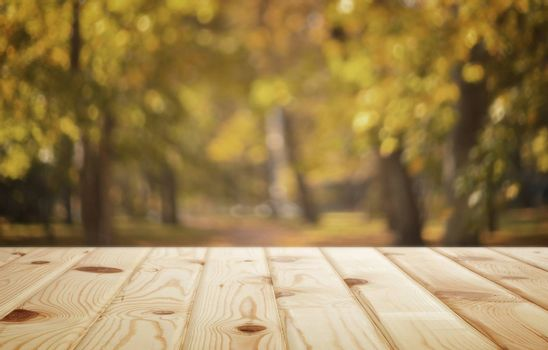 Empty wooden table with autumn Park view in the background for product display mounting
