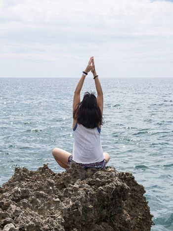 Rear view of young woman with long hair practicing yoga on rocks at sea