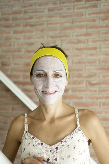 Relaxed woman applies mineral clay mask on face for rejuvenation, has headband on head