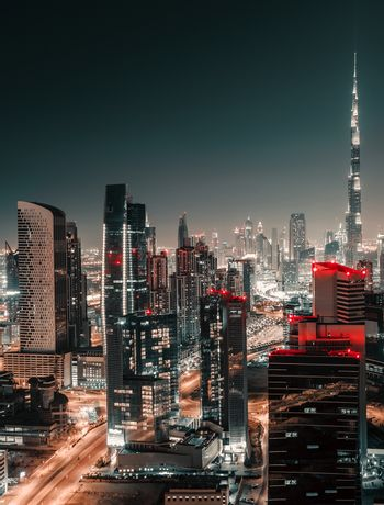 Nighttime Cityscape. Urban Scene Background of a Modern Towers at Night. Lights of Big City. Dubai. United Arab Emirates.