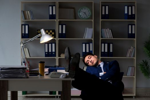 Businessman tired and sleeping in the office after overtime hour