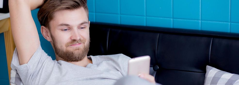 Young man using smartphone for relax on sofa at home, texting message or chatting on phone in internet online on couch for resting, device and technology, communication and lifestyle concept.