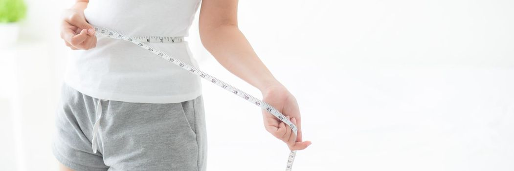 Beautiful young asian woman body diet and slim with measuring waist for weight in the bedroom, girl have cellulite and calories loss with tape measure, health and wellness concept, banner website.